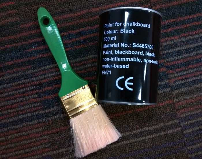 A tin of blackboard paint and a paintbrush
